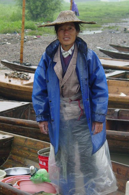 shutterstock_232989 Zhejiang, a woman fisher standing on her boat in a rainy day in Zhejiang China