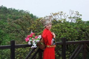 shutterstock_59180779 Hunan, A Hunan lady in traditional attire stand in front a beautiful mountain range